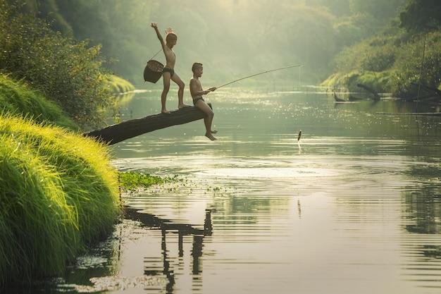 Rapaz asiático a pescar no rio Foto Premium