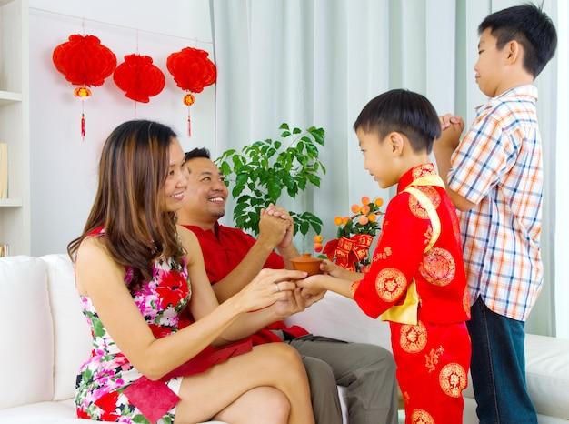 Rapaz asiático apresentando chá para sua mãe durante o ano novo chinês Foto Premium