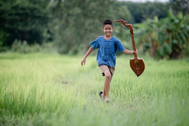 Rapaz asiático com guitarra artesanal no exterior, país de vida Foto gratuita