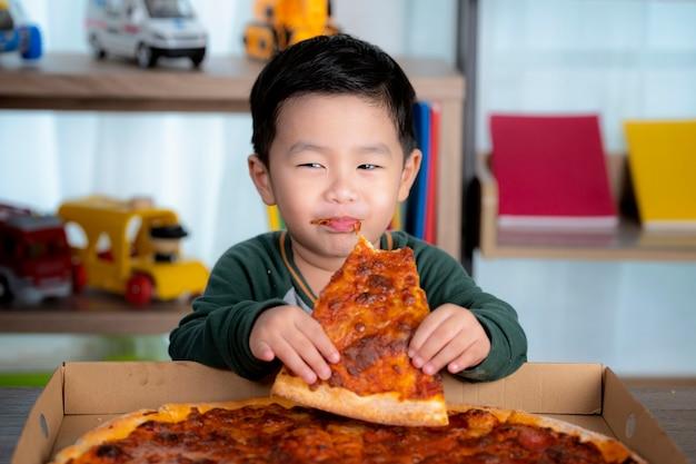 Rapaz asiático comendo pizza e a caixa de pizza colocada sobre a mesa. Foto Premium