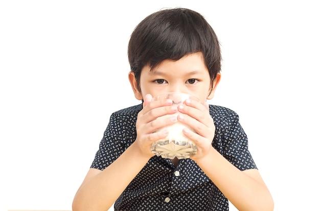 Rapaz asiático é beber um copo de leite sobre fundo branco Foto gratuita