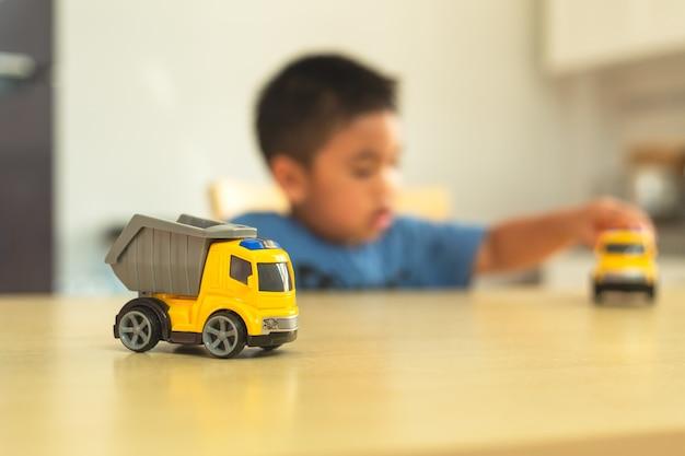 Rapaz asiático está brincando com carros de brinquedo em casa Foto Premium