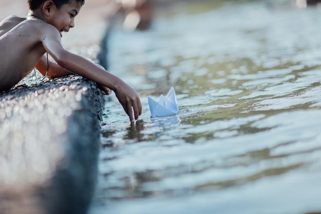 Rapaz asiático jogando barquinho de papel no rio Foto gratuita