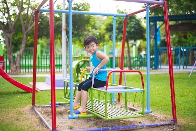 Rapaz asiático jogar um trem de ferro balançando no playground Foto Premium