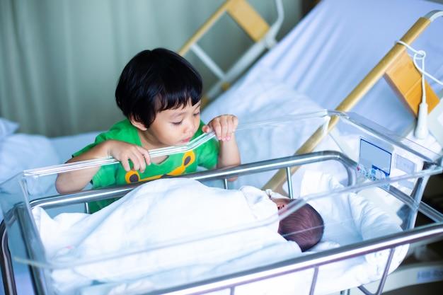 Rapaz asiático, olhando para o irmão recém-nascido Foto Premium