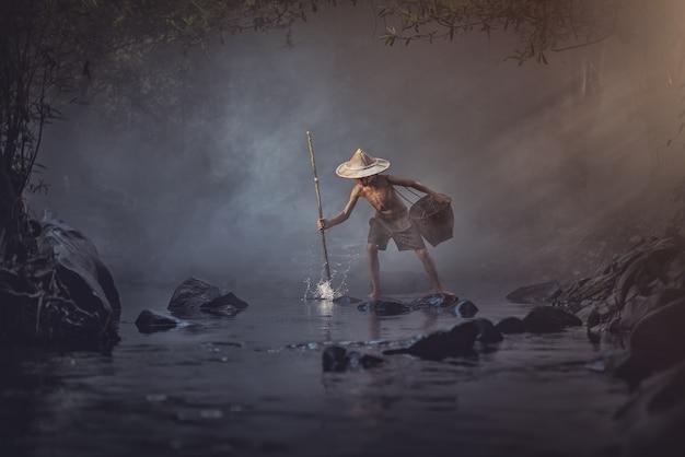 Rapaz asiático pescando no riacho, tailândia rural Foto Premium