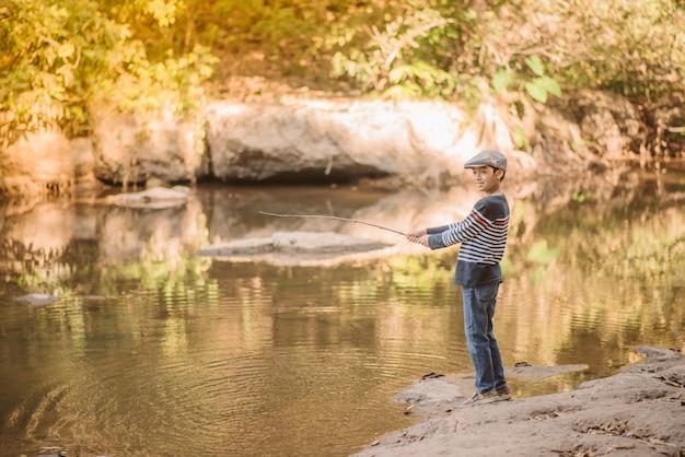 Rapaz asiático pescando no rio vintage retrô Foto Premium