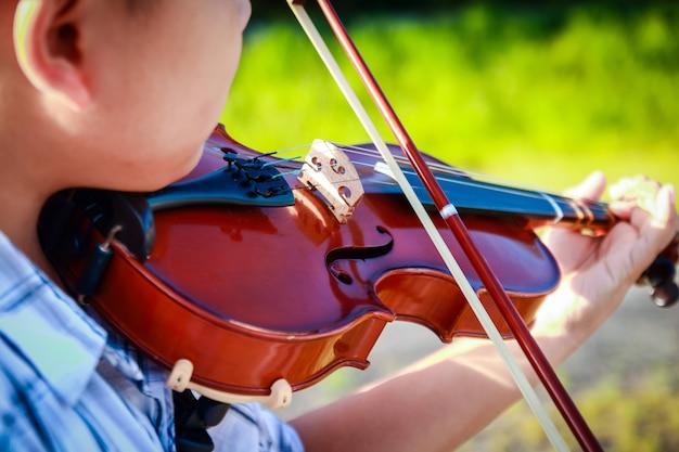 Rapaz asiático tocando violino Foto Premium