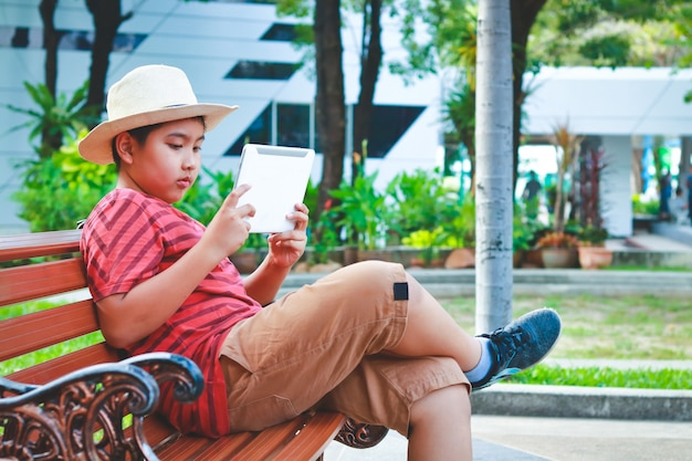 Rapaz asiático usando um chapéu, sentado em uma cadeira, jogando um tablet Foto Premium
