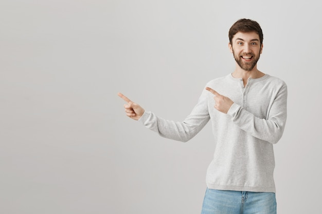 Rapaz barbudo caucasiano apontando o dedo para a esquerda Foto gratuita