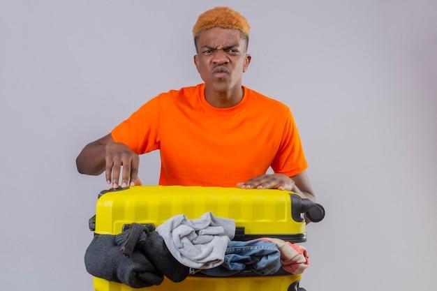 Rapaz carrancudo vestindo uma camiseta laranja em pé com uma mala de viagem cheia de roupas com uma expressão de raiva no rosto sobre a parede branca Foto gratuita