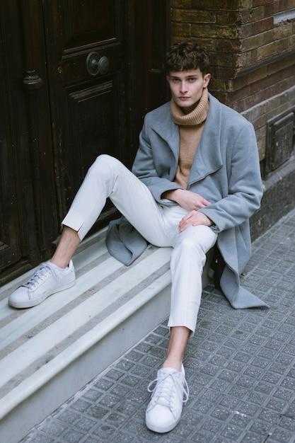 Rapaz com casaco sentado na porta da frente Foto gratuita