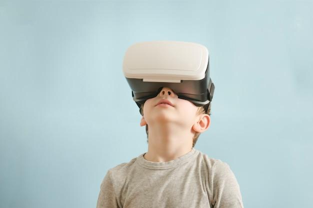 Rapaz com óculos de realidade virtual. fundo azul Foto Premium