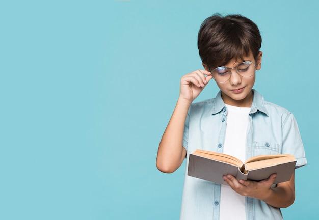 Rapaz com óculos, lendo o tempo Foto gratuita