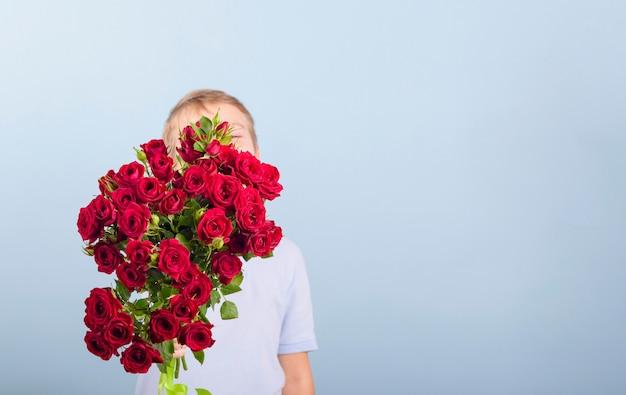 Rapaz com um buquê de rosas vermelhas como presente para o dia das mães ou dia dos namorados Foto Premium