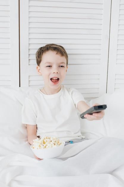 Rapaz comendo pipoca sentado na cama e assistindo tv Foto Premium