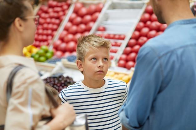 Rapaz, compras com os pais no supermercado Foto Premium