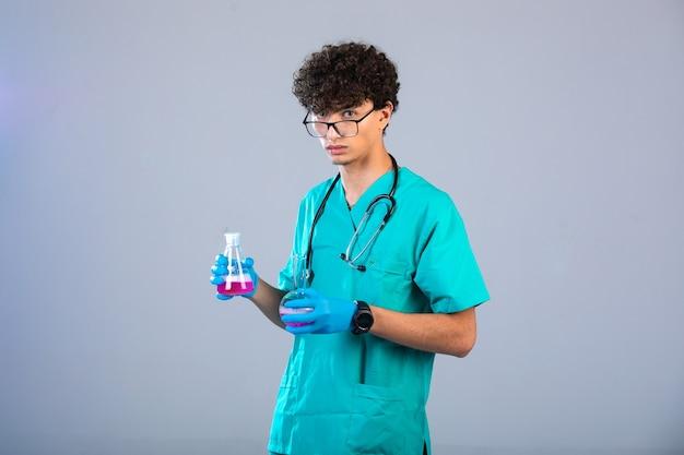 Rapaz de cabelo encaracolado com uniforme médico e máscaras de mão segurando frascos químicos no fundo cinza Foto gratuita
