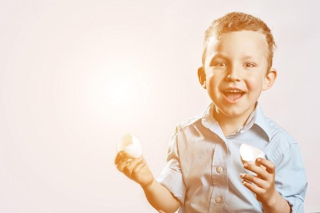 Rapaz de camisa clara, segurando uma casca do ovo e sorrindo Foto Premium