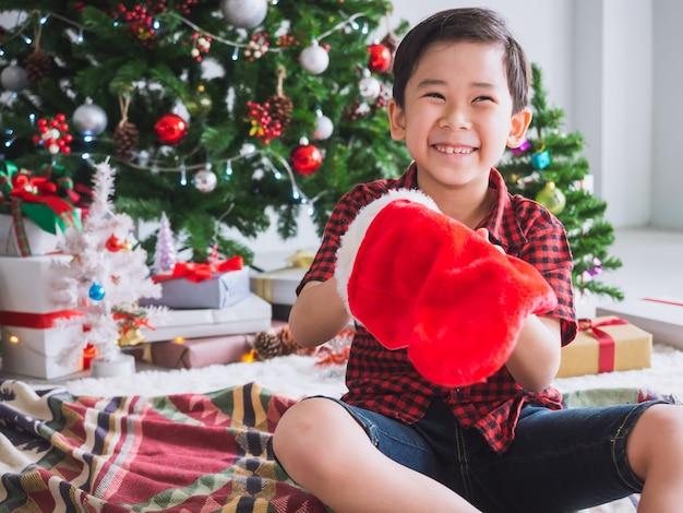 Rapaz de camisa vermelha está segurando a meia vermelha e feliz com engraçado para celebrar o natal com árvore de natal Foto Premium