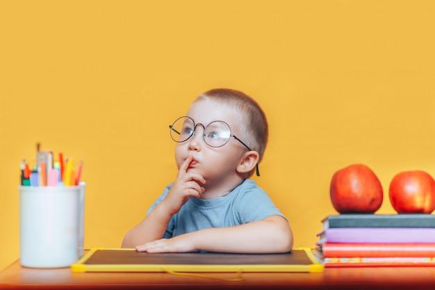 Rapaz de óculos redondos em uma camisa e sentado na mesa e pensando Foto Premium