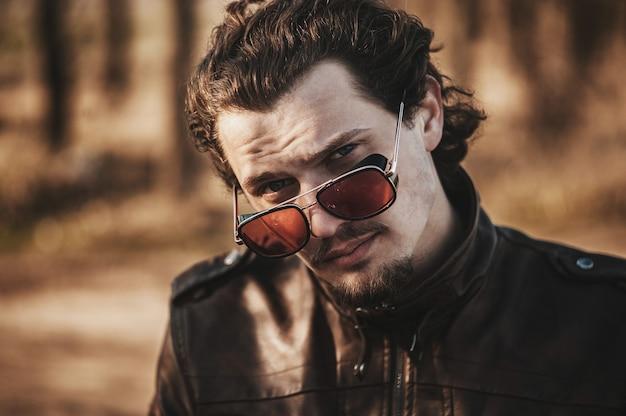 Rapaz encaracolado antiquado em jaqueta de couro, vislumbre atrevido sobre óculos vermelhos. Foto Premium