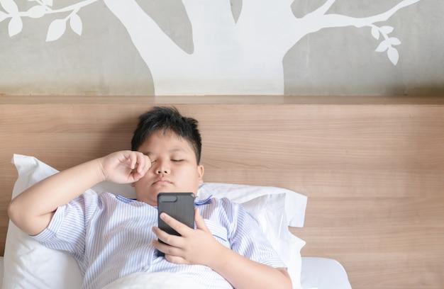 Rapaz esfregando os olhos depois de jogar smartphone Foto Premium