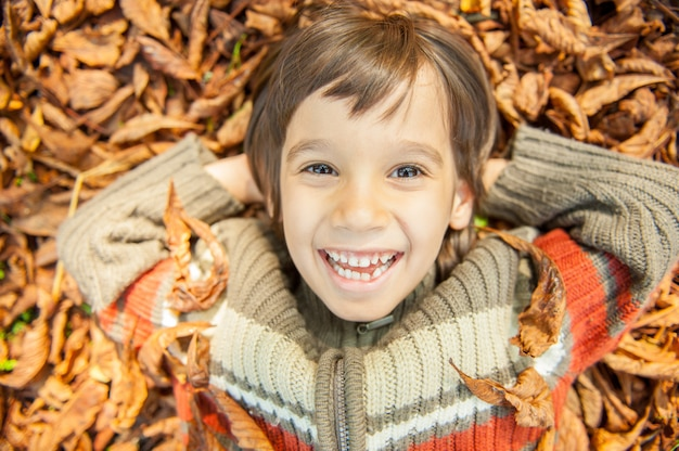 Rapaz estabelece em folhas secas Foto Premium