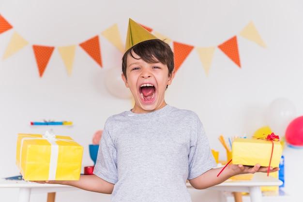 Rapaz excitado com a boca aberta segurando presentes de aniversário na mão Foto gratuita