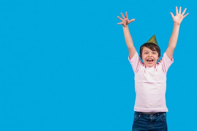 Rapaz excitado levantar as mãos na frente da superfície azul Foto gratuita