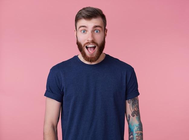 Rapaz jovem atraente de barba vermelha chocado com olhos azuis, vestindo uma camiseta azul, olhando para a câmera com a boca aberta e gritando de surpresa isolado sobre fundo rosa. Foto gratuita