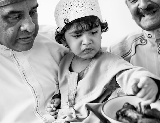 Rapaz muçulmano comendo datas secas Foto gratuita