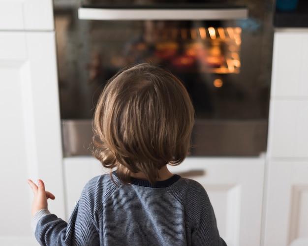 Rapaz olhando para o forno Foto gratuita