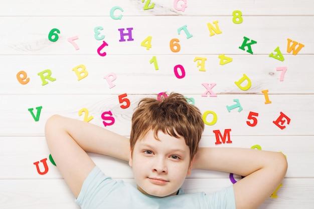 Rapaz pequeno com as letras do alfabeto do arco-íris que colocam no assoalho de madeira. Foto Premium