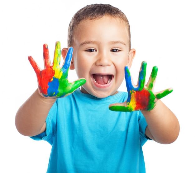Rapaz pequeno com as mãos cheias de tinta e com a boca aberta Foto gratuita
