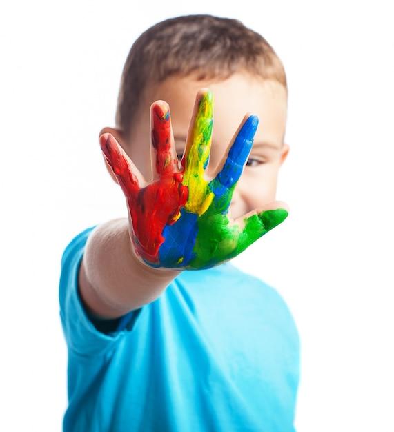 Rapaz pequeno com uma mão cheia de tinta cobrindo o rosto Foto gratuita