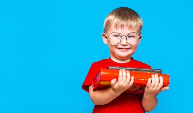 Rapaz pequeno de sorriso nos vidros redondos que guardam uma pilha de livros. educação. pronto para a escola Foto Premium