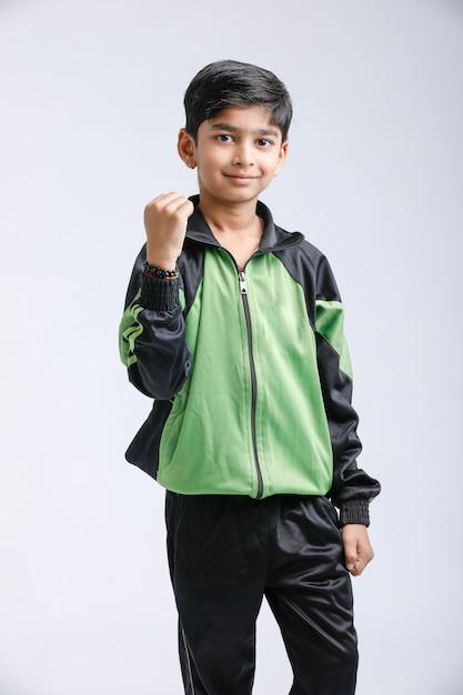 Rapaz pequeno indiano bonito que joga e que dá a expressão múltipla Foto Premium