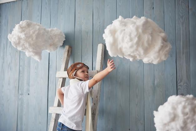 Rapaz pequeno no chapéu do piloto que está na escada no. chegar ao céu. tocar as nuvens Foto Premium