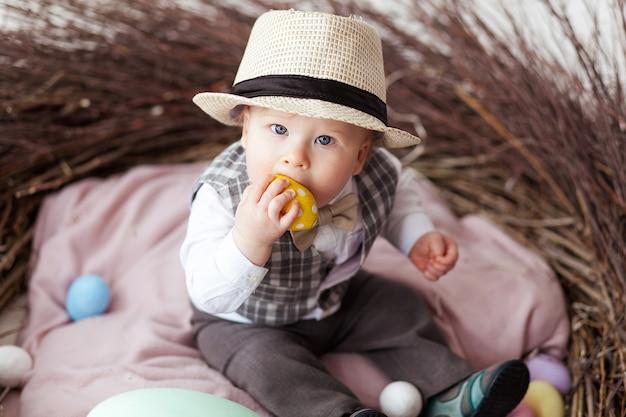 Rapaz pequeno no chapéu que senta-se no ninho e que come o ovo da páscoa. Foto gratuita