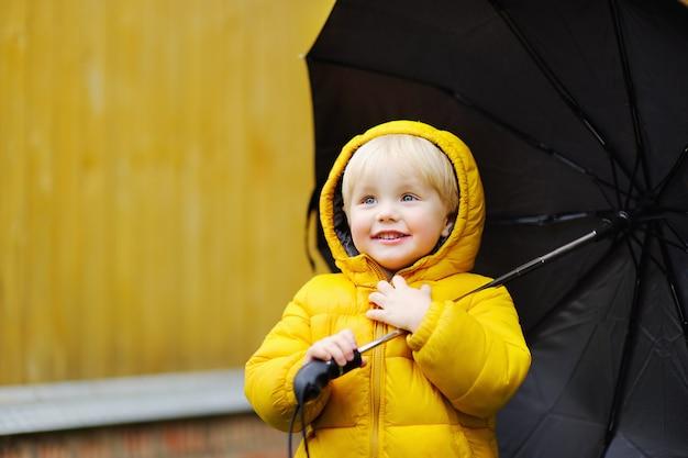 Rapaz pequeno que anda no tempo nebuloso chuvoso do outono. criança com guarda-chuva preta grande na chuva. atividade ao ar livre Foto Premium