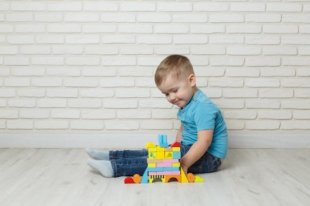 Rapaz pequeno que joga com o construtor no fundo branco. menino jogando blocos brinquedos Foto Premium