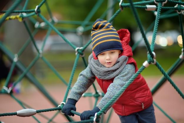 Rapaz pequeno que joga na terra moderna do jogo de crianças. Foto Premium