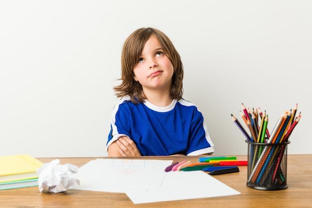 Rapaz pequeno que pinta e que faz trabalhos de casa em sua mesa infeliz. Foto Premium