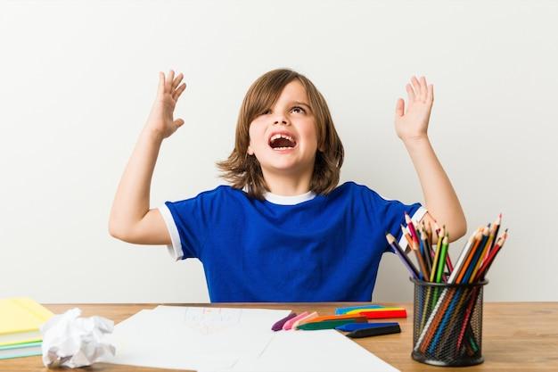Rapaz pequeno que pinta e que faz trabalhos de casa em sua mesa que grita ao céu. Foto Premium