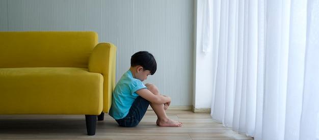 Rapaz pequeno que senta-se ao lado do sofá amarelo em casa. autismo infantil. Foto Premium