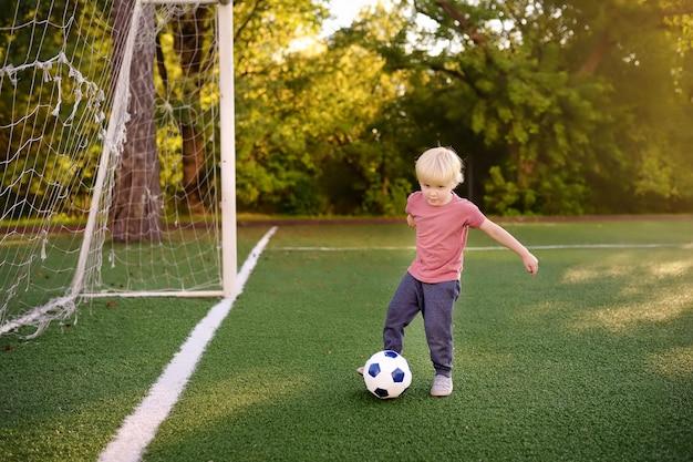 Rapaz pequeno que tem o divertimento jogar um futebol / jogo de futebol no dia de verão. Foto Premium