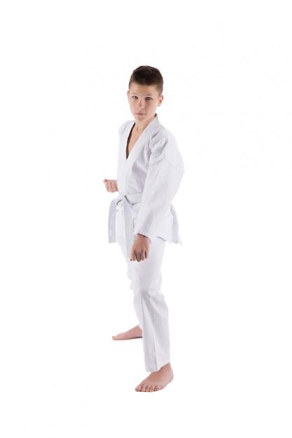 Rapaz posando com técnicas de karatê em branco isolado Foto Premium