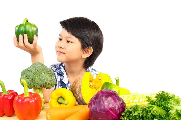Rapaz saudável asiático mostrando expressão feliz com variedade vegetal colorido fresco Foto gratuita