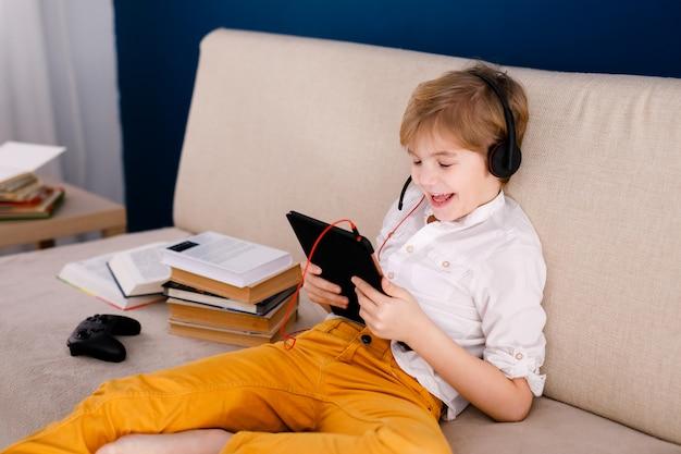 Rapaz sentado no sofá, comendo pipocas e brincando com o gamepad durante sua aula on-line em casa, distância social durante a quarentena, auto-isolamento, conceito de educação on-line Foto Premium